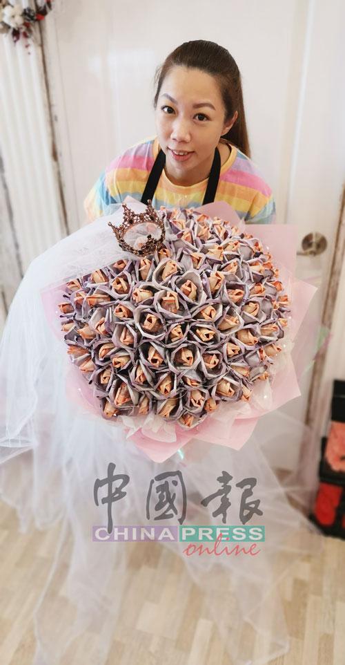 郑爱妮拿着2万令吉现金制成的纸钞玫瑰花,有车轮胎那么大。