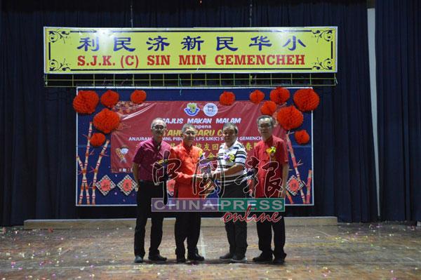 周金财(左2)赠送纪念贺盾给荣获第三届世界杰出华人青年企业家奖的校友王维浚博士,由其父亲王祚福代领,左起为李惠南及黄志东。