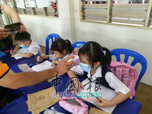 校方帮学生量体温,确保学生的健康状况。
