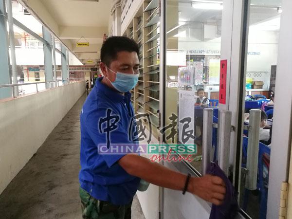 校工在爱群二校课室进行消毒清洁工作。