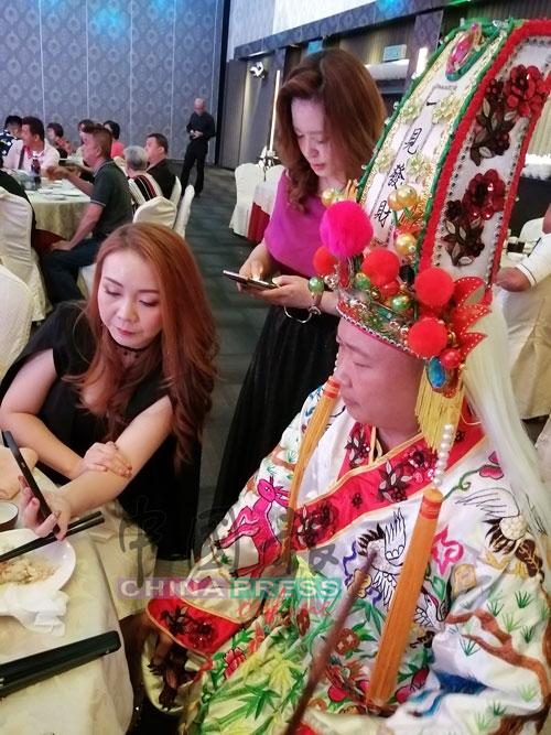 大爷伯(右)观看圣皇殿理事通过神庙面子书专页的直播视频。