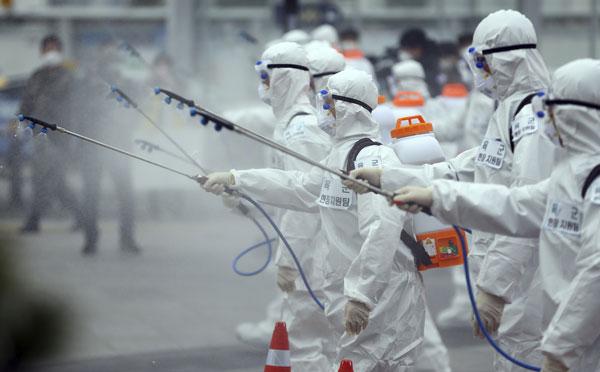 身穿防护服的韩国陆军士兵,周六在大邱火车站喷洒消毒液。(美联社)