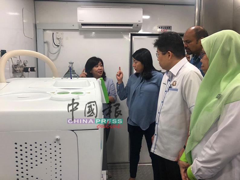 杨美盈(左2)在陈正春、纳古及诺琳陪同下,巡视流动车上的气体检测器运作。