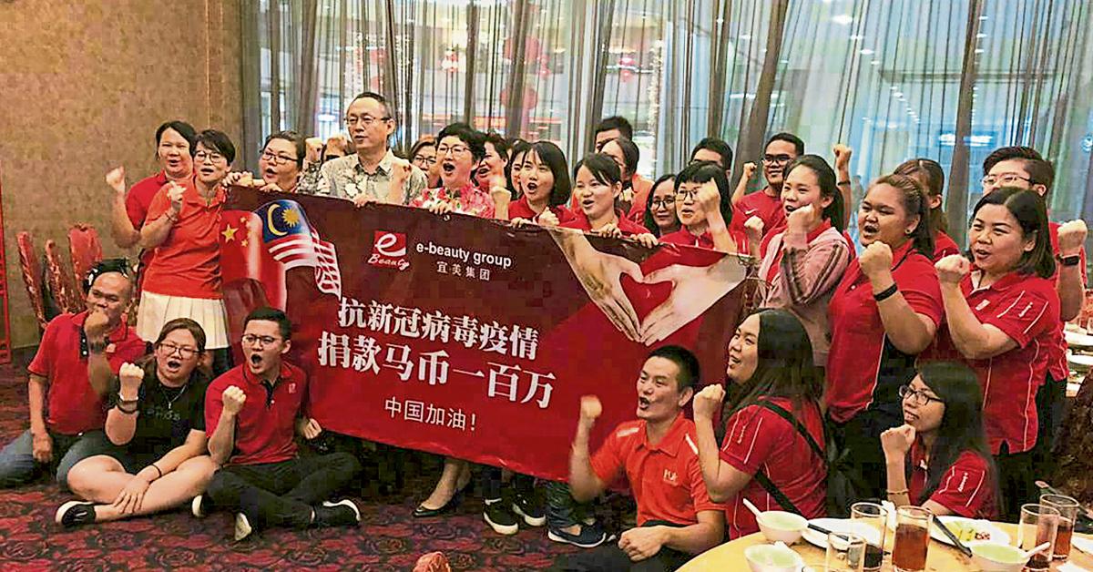 张国顺(第2排左4起)、曲锾与管理层及职员,为中国抗新冠肺炎疫情,高呼加油。
