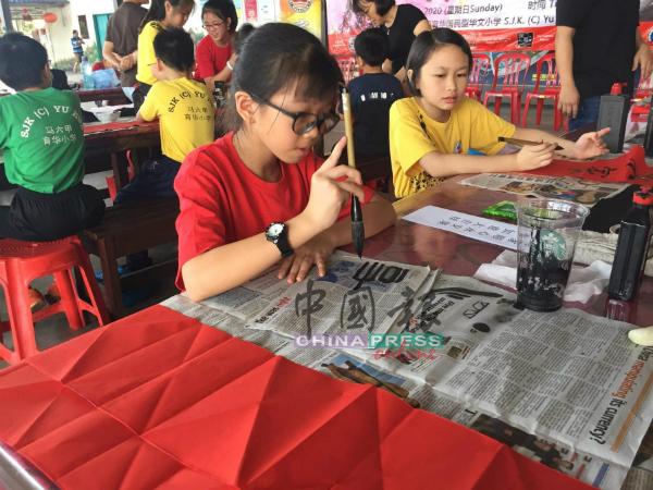 小学参赛者认真地按照赛事主题进行挥毫。