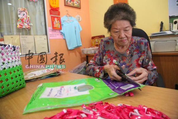 郑宝玲将米袋清洗乾净后进行裁剪工作。