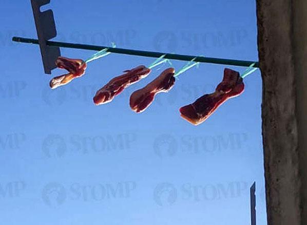 居民将4块肉挂在竹竿,放在厨房窗口外晾晒。(受访者提供)