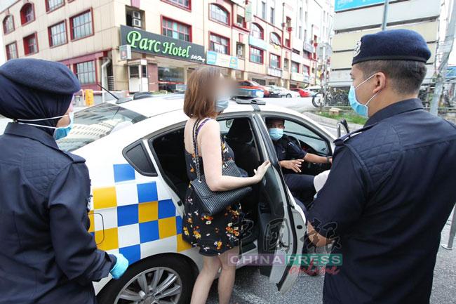 警员把女子带上警车,准备押回警局录口供。