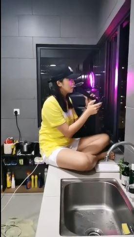 女子坐在自家厨房,透过窗口向公寓其他住户大开个人演唱会。