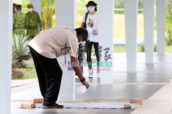 工作人员在地毯上喷射消毒药水。