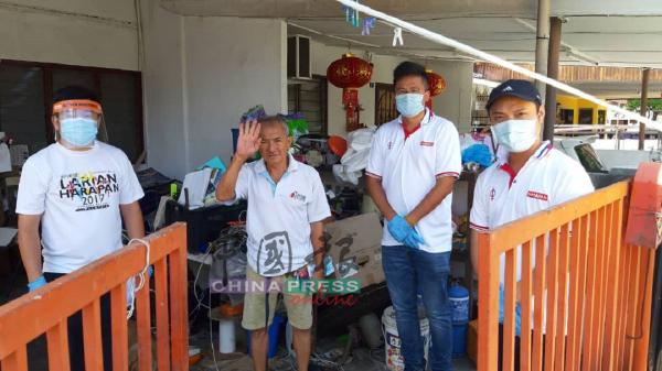 谢守钦(右2)移交物资给一名捡纸皮的老伯。左为张文杰。
