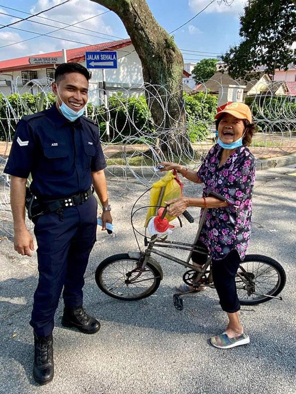老妇开心的和协助她的警员合照。
