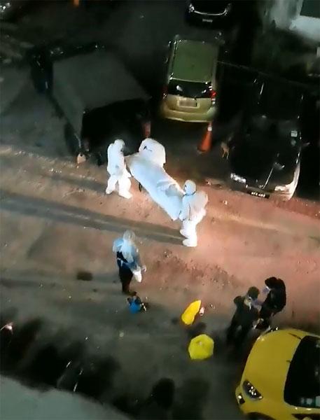 医护人员全副武装将死者遗体抬上救护车,严阵以待的阵容在网络上被传与病毒有关。