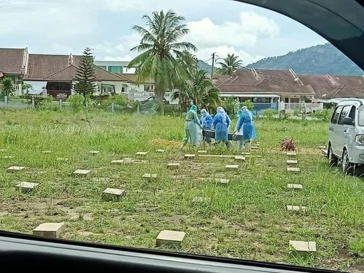 穿上防疫衣的葬礼工作人员顶着烈阳,将死者棺木抬入指定的墓园。