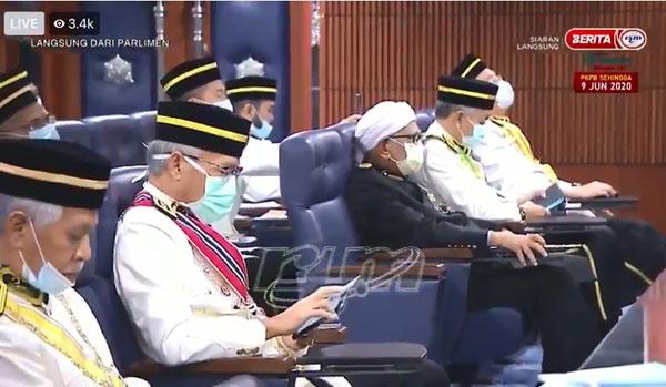 纳吉(右起)、阿末扎希及哈迪阿旺坐在执政党座位,其中纳吉和哈迪阿旺在议会厅内闭目养神,阿末扎希则在滑手机。