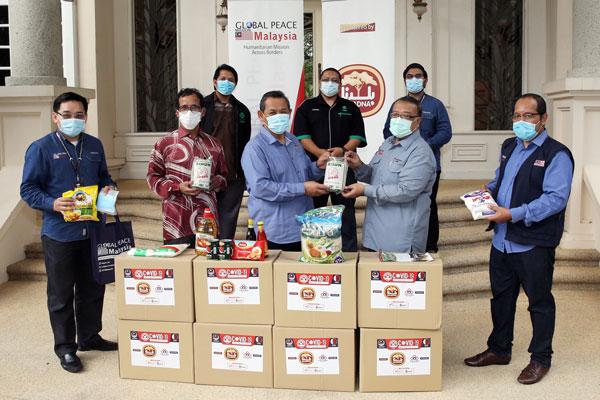 全球和平组织捐献1000份粮食援助箱,提供给有需要的家庭,前排左起阿末法米、拉查里、阿米努丁及莫哈末哈林米。