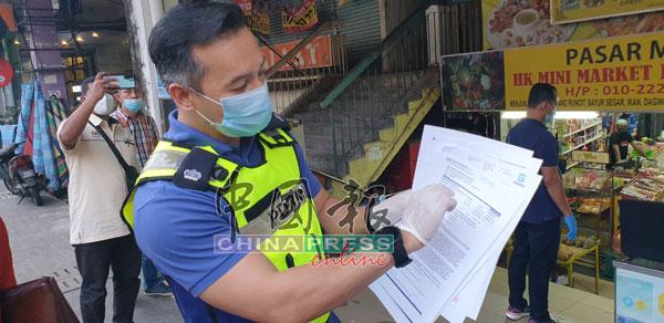率队警官阿纳斯副警监展示警方起获的新冠肺炎检测假报告。