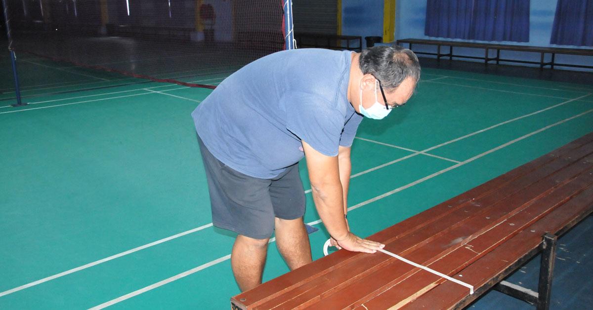 叶国斌在椅子上贴上贴纸作为记号,为羽球馆重开做好准备。