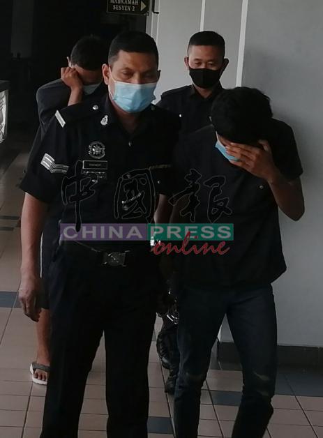 莫哈末哈金海卡(前右)和艾曼阿菲(后左),被带离法庭时低头并用手遮脸。