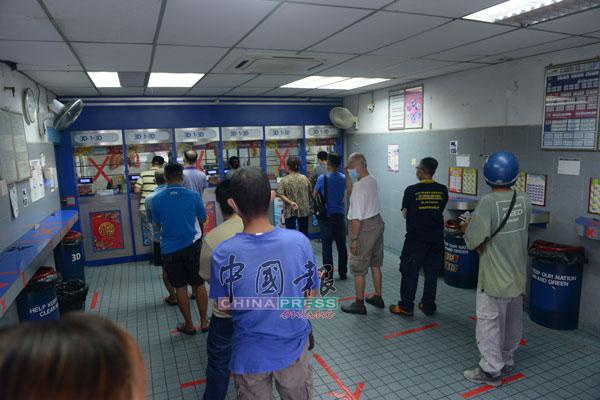 博彩店内的地上已贴好红色胶带,以提醒顾客保持1公尺距离排队。