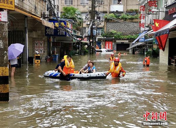 湖北省宜昌市消防人员用橡皮艇协助灾民撤离灾区。(中新网)