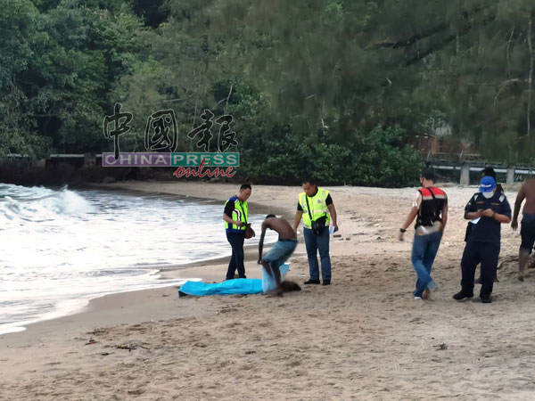 不幸溺毙者的尸体随着波浪被冲至浅海处,民众和消拯员合力移上岸边。