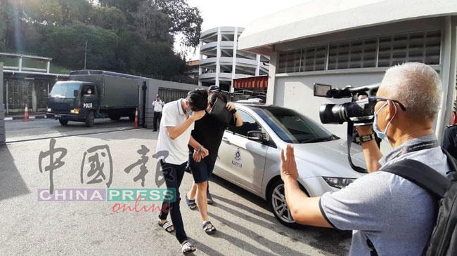 刘佳荣(左起)和邝健明被铐上手铐,被押往推事庭面控。