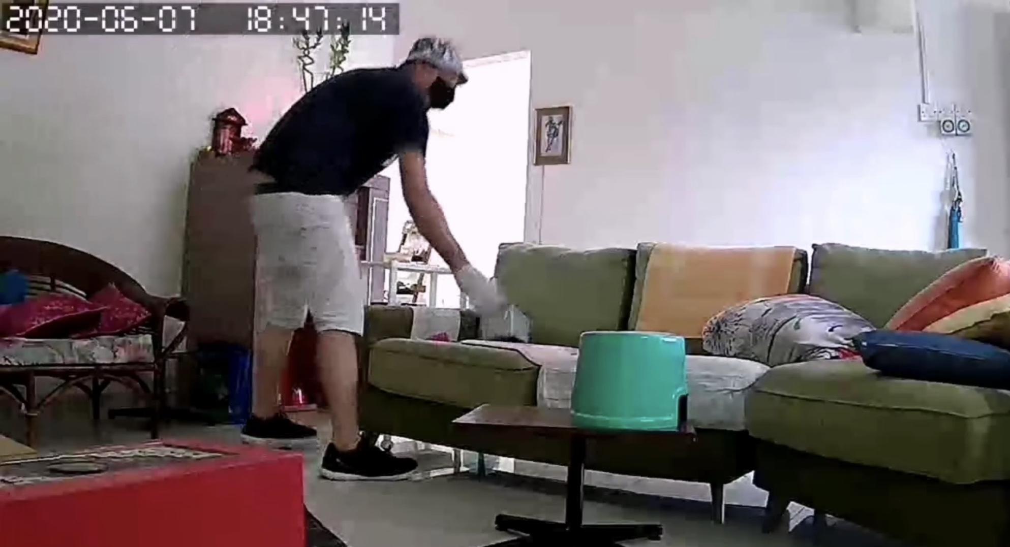 其中一个黑衣男在客厅翻找时,丝毫没察觉到放在一旁的监视器。