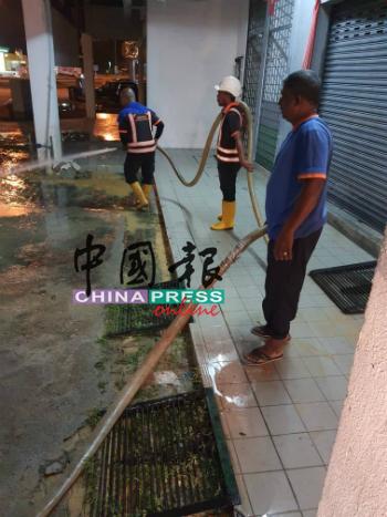 水务公司员工在完成水管提升工程后,已清洗现场的泥浆。