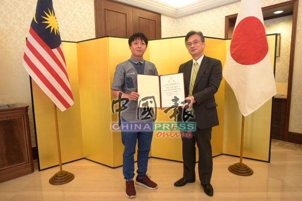 蓝国清(左)接获冈浩(右)颁发的奖状。