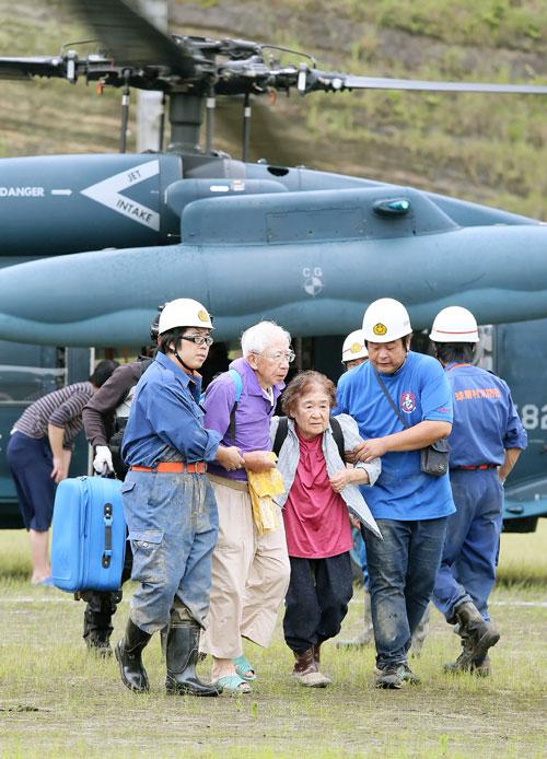 日本自衛隊成員用直升機載老人撤離災區。(法新社)
