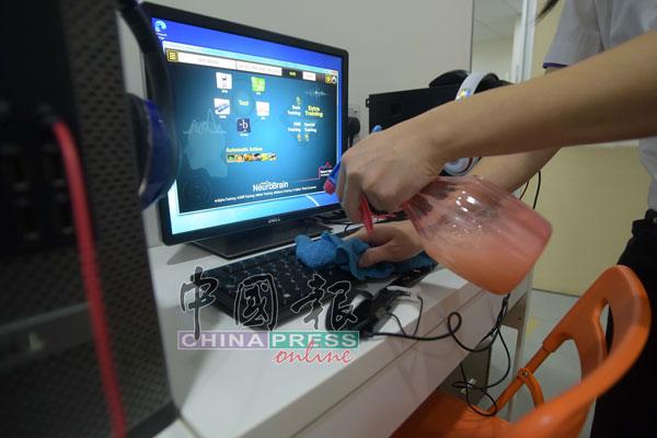员工使用消毒剂擦洗电脑键盘。