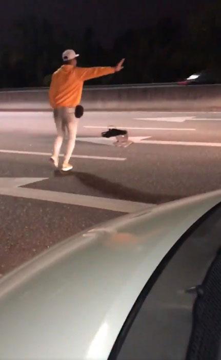 男子将轿车停泊在一旁,趁着没有车辆经过时,跑到路中央。