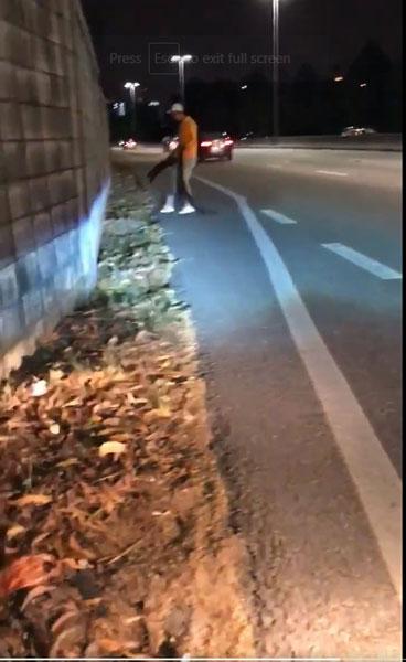 男子安全走回路旁,并将轮胎弃在一旁。