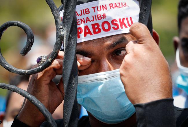 纳吉支持者得知纳吉7项控状罪成后难过拭泪。