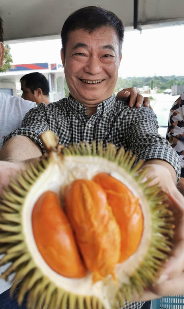 一脸惊喜的廖伟雄捧着红肉的山榴梿。