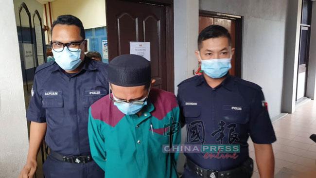 被告(中)被庭警押往法庭扣留室。