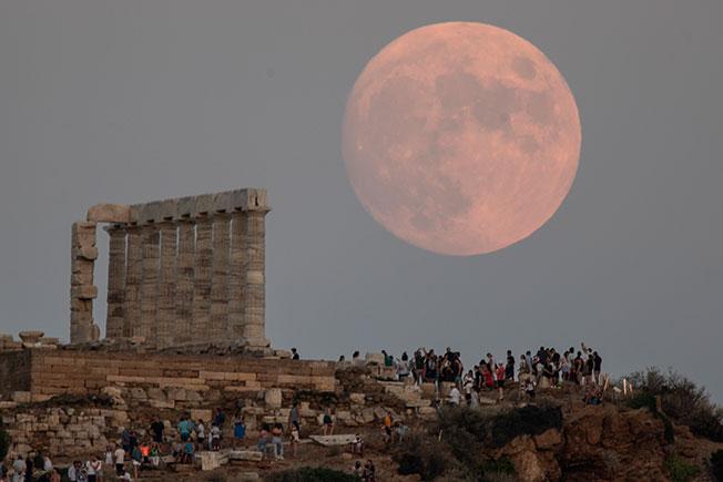 希腊雅典民众2日看月亮,月亮在海角苏尼恩海神波塞冬神庙的柱子后面升起。