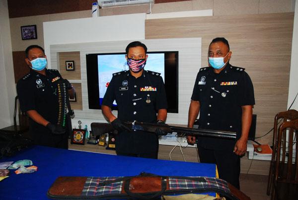 莫哈末凯里(中)展示警方寻获的失枪。