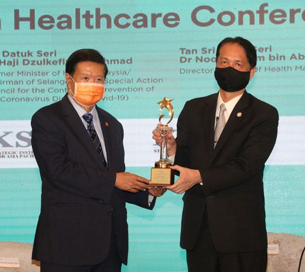 诺希山(右)获颁全国公共卫生领导力终身成就奖项,他从皇岦策略研究院院长丹斯里杨元庆手中接过奖项。