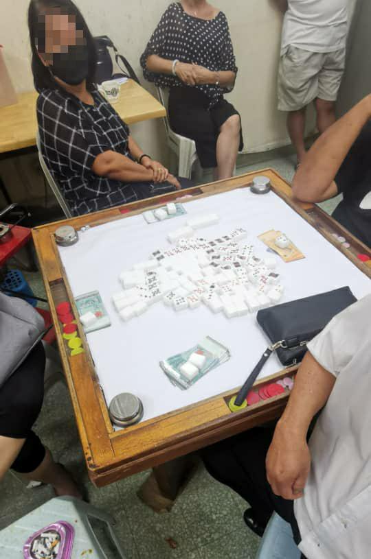 警方上门突击时,在场男女正围在麻将桌前打麻将。