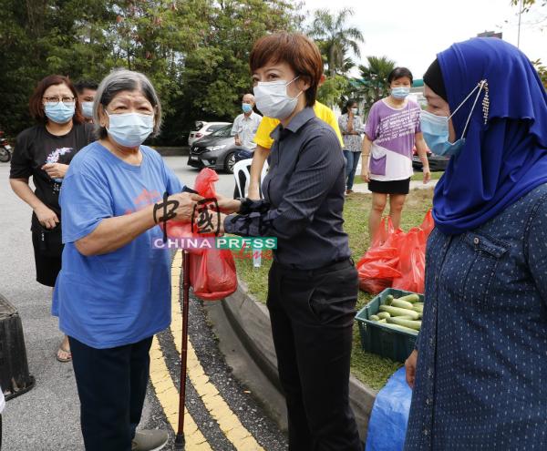 陈丽群(右2)将热心小贩捐助的物资派发给受惠者。
