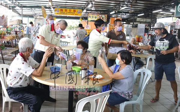 叶耀荣(站左)与团队们一起派发口罩给民众,提醒民众记得戴口罩,也切勿乱丢用后的口罩。