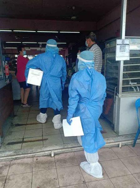斗湖卫生局医护人员前往金花园角头店铺式菜市场依照程序进行消毒工作。