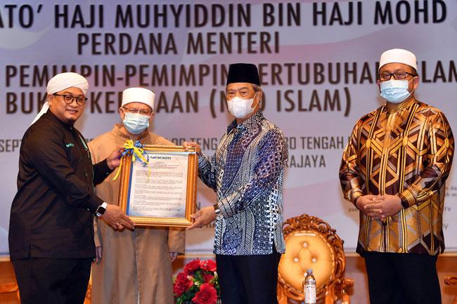大馬伊斯蘭宣教基金會(YADIM)主席納斯魯丁(左)將大會議案交給慕尤丁(右2),左2起為祖基菲莫哈末及阿末馬祖。