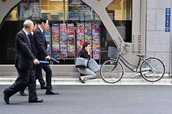 日本东京街头,一名女性上班族蹲在布告栏前讲手机。