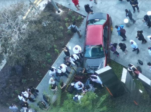 20名公众合力抬车,解救困在车底的女郎。(档案照)