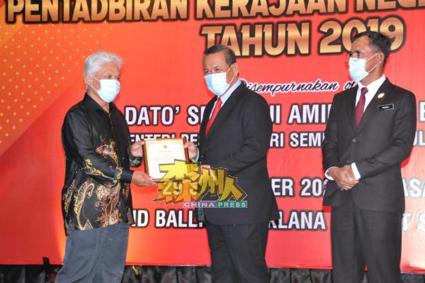 阿米努丁(中)颁发表扬状予退休公务员,右为拉查里。