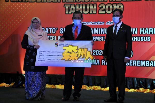 阿米努丁移交5万8400令吉予国家高等教育基金局森州分局,由主任艾因舒哈拉接领模拟支票。