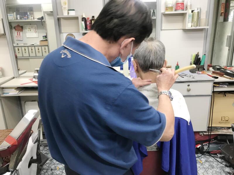 黄坤生秉持46年传统手艺,为顾客理起发来态度一丝不苟。如今疫情期间,刮脸、修眉和挖耳等服务都已暂停。